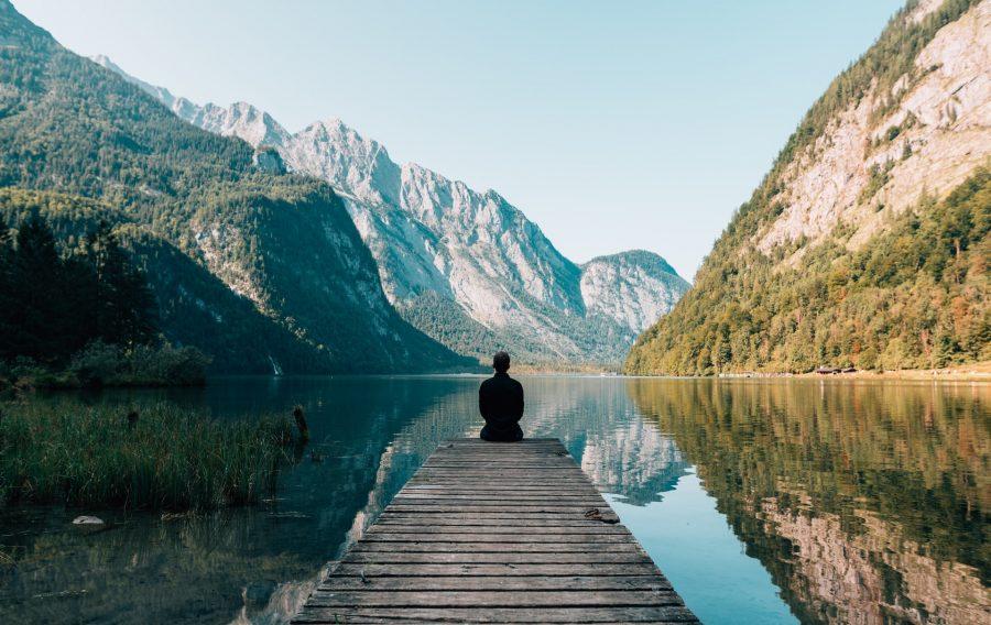 persona-en -embarcadero-lago-montañas
